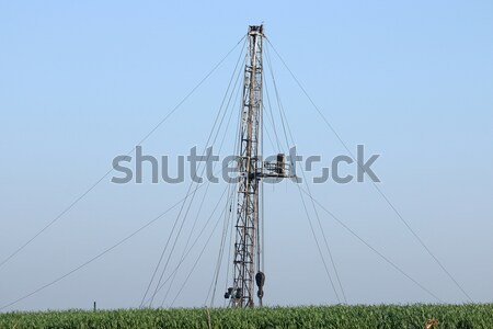 oil drilling rig behind green wheat field Stock photo © goce