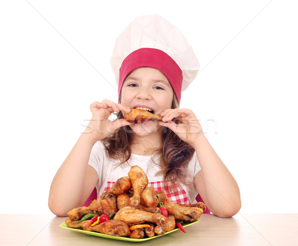 hungry little girl cook eating chicken drumstick Stock photo © goce