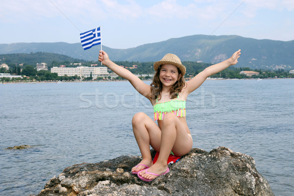 happy little girl sitting on a rock by the sea and waving Greek  Stock photo © goce