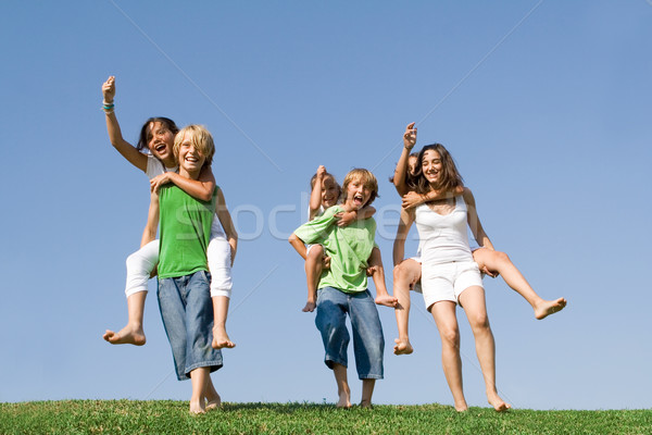 group of kids at summer camp or school having piggyback race. Stock photo © godfer