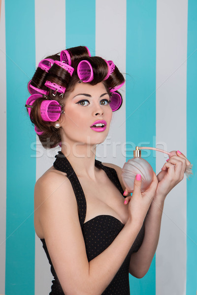 retro pin up girl spraying perfume with hair rollers Stock photo © godfer