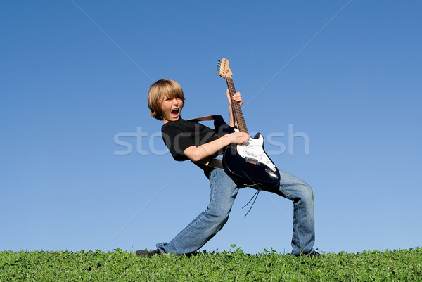 child playing guitar and singing Stock photo © godfer