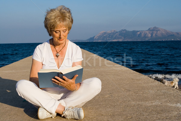 senior woman sitting on beach reading book on summer vacation in mallorca Stock photo © godfer