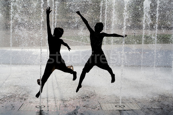 Silhouette enfants sautant cool fontaine eau Photo stock © godfer