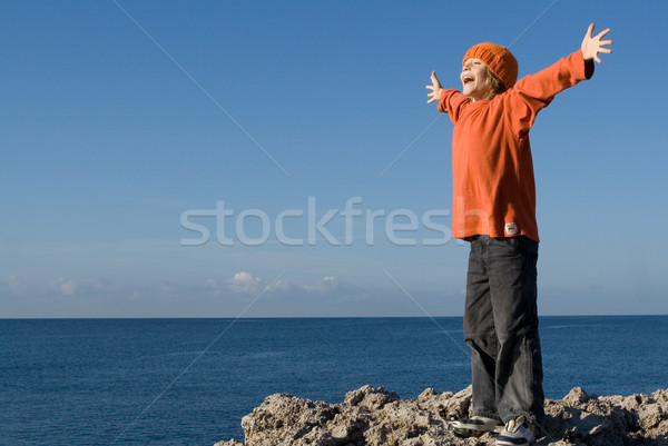 happy child on vacation shouting or singing with arms outstretched Stock photo © godfer
