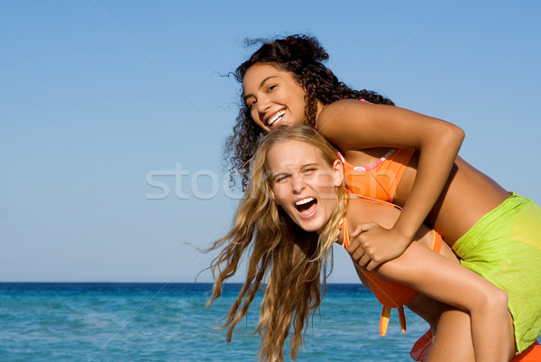 Stock photo: diversity, mixed race friends playing piggyback on summer holiday at beach
