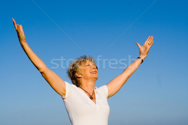 happy christian senior woman arms raised in faith and praise Stock photo © godfer