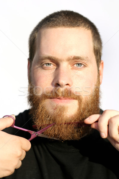 Stock photo: bearded man trimming or cutting beard with scissors