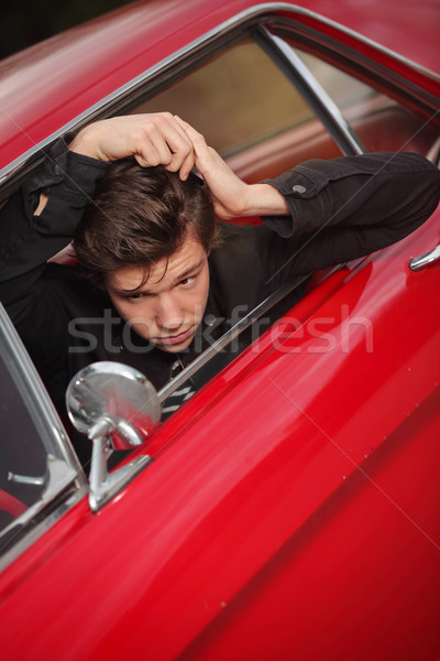 young rocker combing hair in fifties car Stock photo © godfer