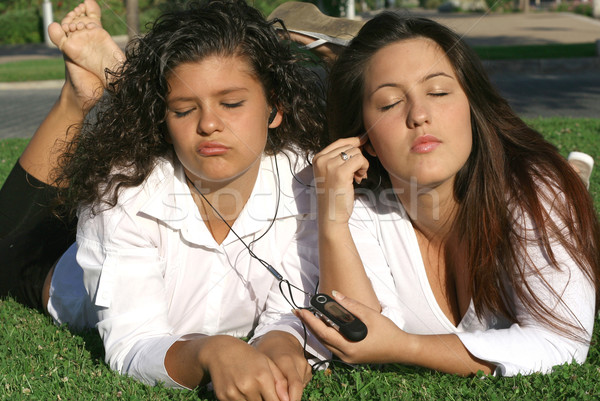 teens students relaxing on campus listening to music sharing earphones and personal stereo Stock photo © godfer