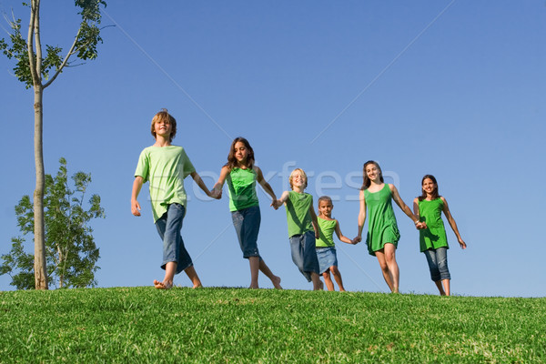happy group of summer camp or school kids holding hands Stock photo © godfer