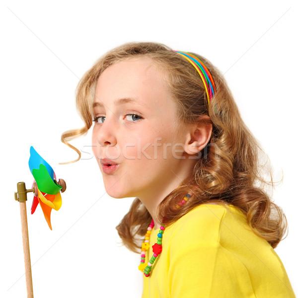 Csinos lány fúj szélmalom gyermek mutat Stock fotó © godfer