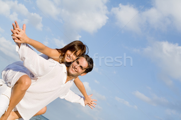 happy couple on holiday vacation or honeymoon piggyback fun Stock photo © godfer