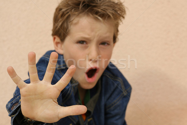 Stock photo: defiant or abused boy angry or frightened hand out