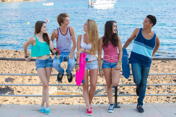 group of diverse mixed race teens hanging out at beach.  Stock photo © godfer
