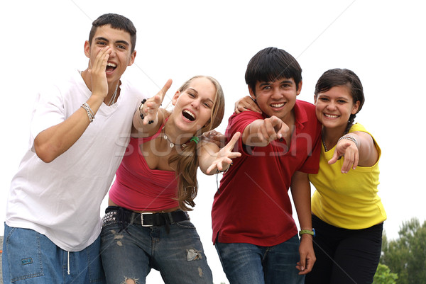 group of happy smiling diverse teens calling or shouting Stock photo © godfer