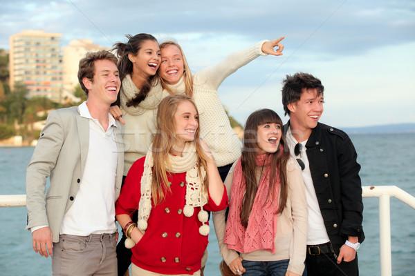 Groupe heureux étonné adolescents jeunes pointant Photo stock © godfer