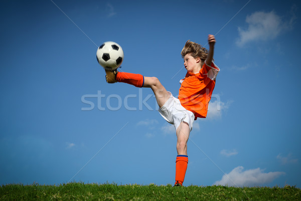 Child kicking playing football. Stock photo © godfer