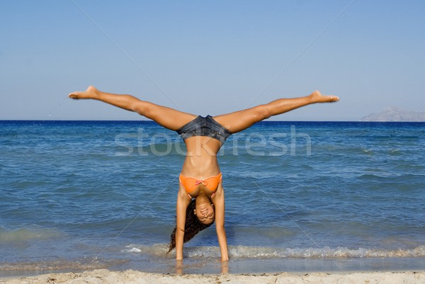 happy woman doing cartwheel or handstand on summer beach holiday in mallorca Stock photo © godfer