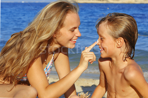 mother putting sun cream on child in summer Stock photo © godfer