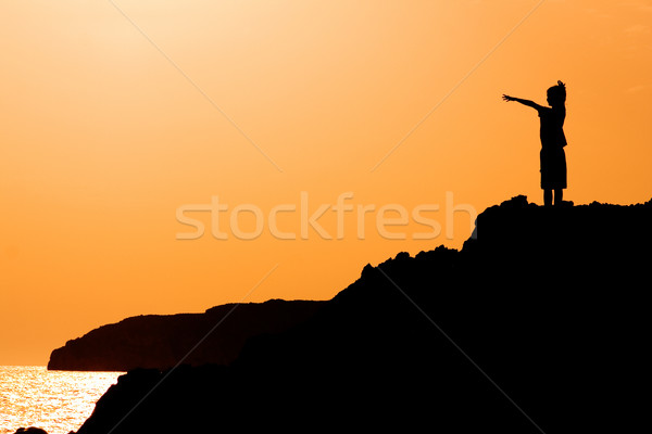 child with arms raised in joy at the vacation sunset Stock photo © godfer
