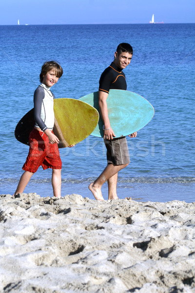 healthy fit active child with surf instructor or teacher on beach summer vacation Stock photo © godfer