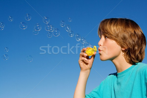 happy kid blowing bubbles with bubble wand Stock photo © godfer