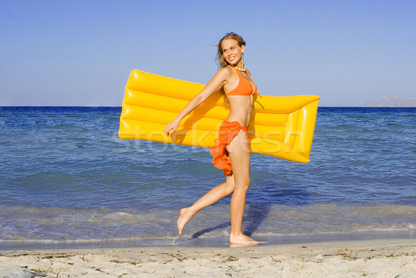 happy young woman walking on beach with airbed on summer vacation Stock photo © godfer