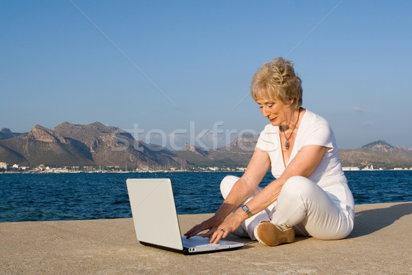 global communication, senior woman on internet on vacation Stock photo © godfer