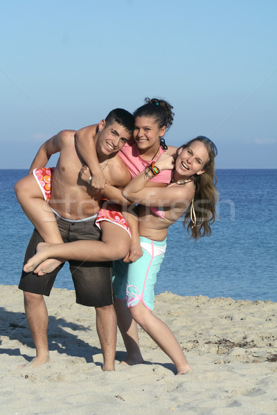smiling group of youth, kids,or teenagers playing, piggyback on beach summer holiday Stock photo © godfer