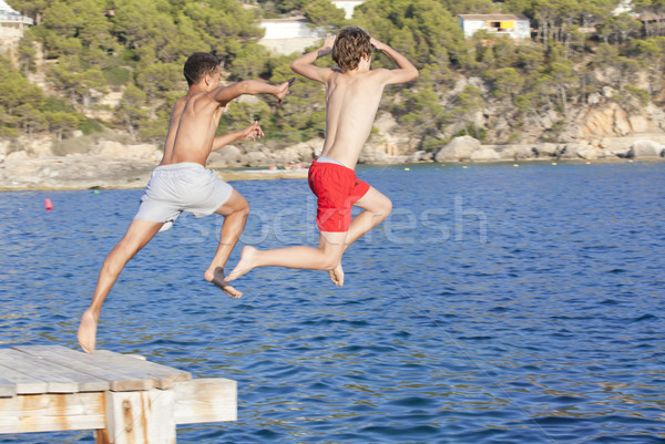 summer camp kids jumping in sea Stock photo © godfer