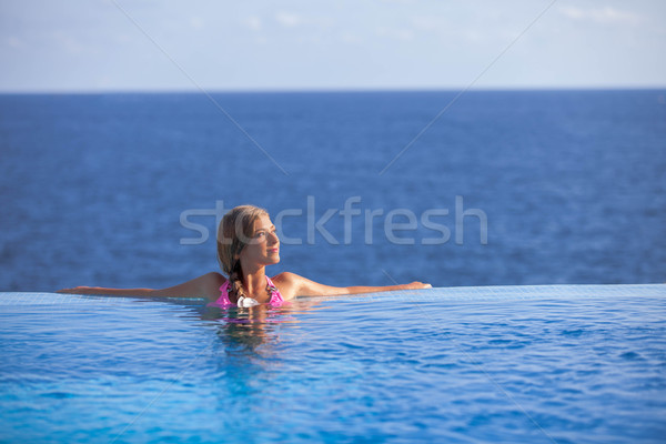 woman relaxing in infinity pool in summer Stock photo © godfer