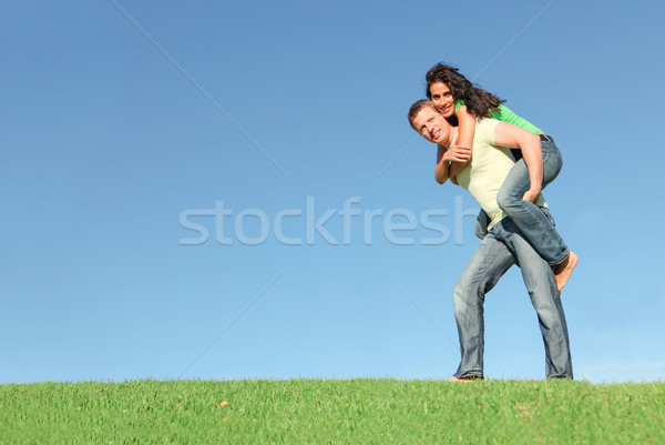 happy smiling couple outside on grass giving piggy back Stock photo © godfer