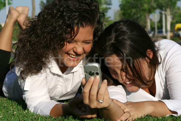 students on campus with mobile or cell phone laughing and having fun Stock photo © godfer