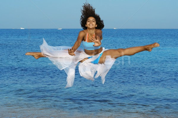 happy woman doing splits leap on beach on vacation Stock photo © godfer