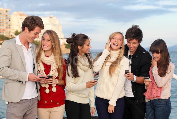 Stockfoto: Tieners · mobiele · mobiele · telefoons · groep · gelukkig · glimlachend
