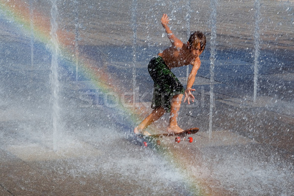 kid cooling off playing on skateboard in fountain Stock photo © godfer