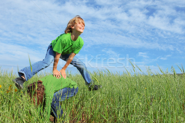 happy healthy kids playing leapfrog Stock photo © godfer