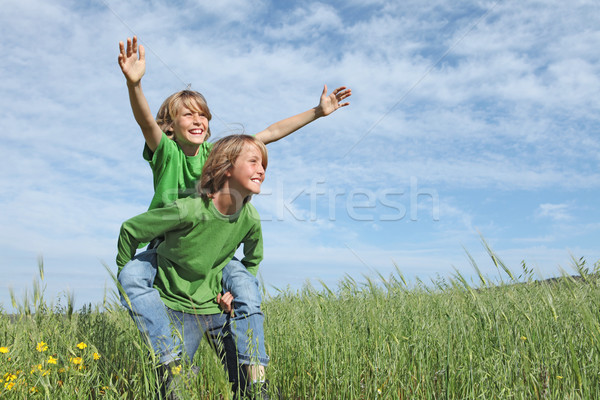 healthy happy fit active kids playing piggyback outside in summer Stock photo © godfer
