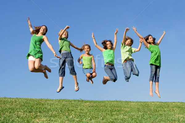 Stock photo: happy group of mixed race kids at summer camp or school jumping