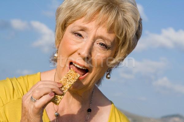 Felice senior donna mangiare sano cereali bar Foto d'archivio © godfer