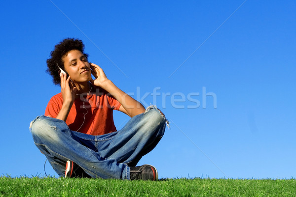 african descent youth listening to music on personal stereo  mp4 or mp3  Stock photo © godfer