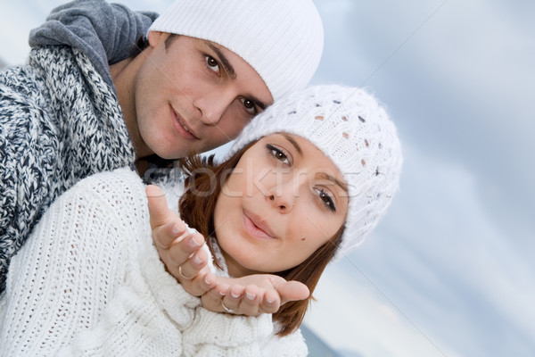 young couple blowing wishes from empty cupped hands Stock photo © godfer