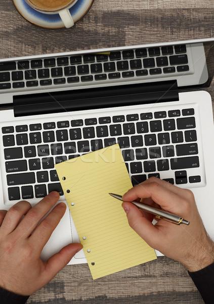 Man at desk taking notes Stock photo © goir