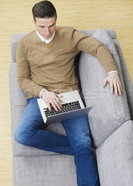 Man on couch with laptop Stock photo © goir