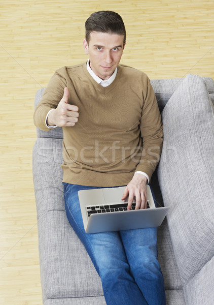 Man on couch with laptop showing ok sign Stock photo © goir