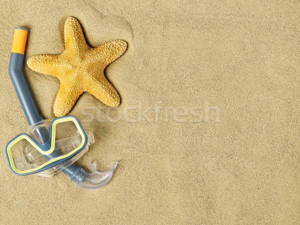 Starfishes and swimming goggles on sand Stock photo © goir