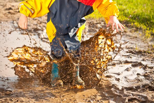 Child splashing in muddy puddle Stock photo © grafvision