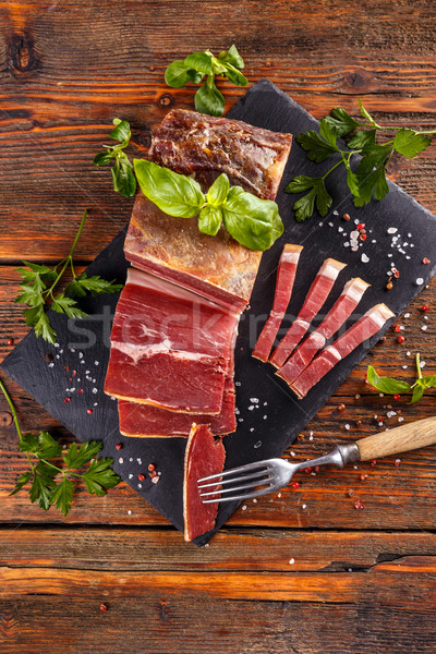 Prosciutto sliced on black slate Stock photo © grafvision