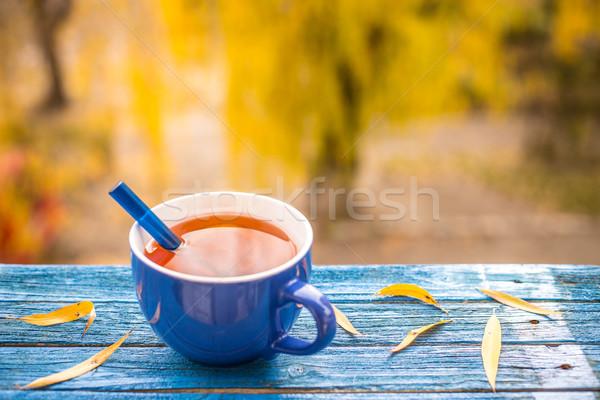 Teáscsésze fa asztal elmosódott őszi naplemente levél Stock fotó © grafvision